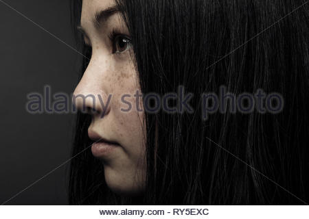 Close up profile portrait thoughtful beautiful teenage girl with black hair, brown eyes and freckles - Stock Photo