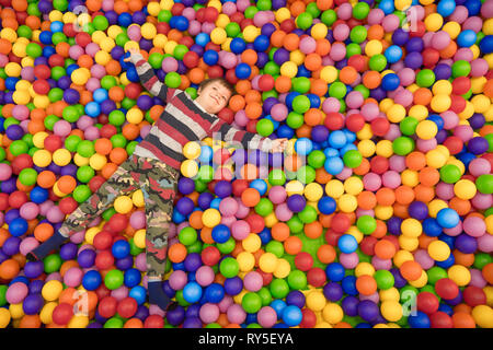 Baby boy spending time in the pool filled with balls. Indoor activities. Leisure time for children. Kid plays with colorful plastic balls at - Stock Photo