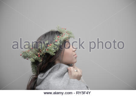 Profile portrait beautiful serene young Jamaican woman wearing christmas wreath on head - Stock Photo