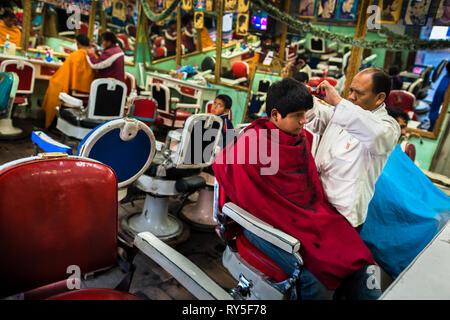 A Peruvian hairdresser cuts a boys's hair in a vintage barber shop in Cuzco, Peru. - Stock Photo