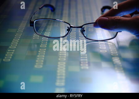 hand reaching for glasses on digital led displaying multiple layers of binary code computer data matrix. big data analytics and digital language conce - Stock Photo