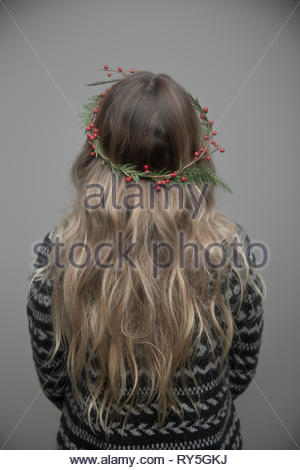 Rear view portrait young woman with long blonde hair wearing christmas wreath in hair - Stock Photo