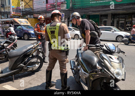 Thailand traffic police. Motorcyclist receiving ticket from Thailand traffic policeman - Stock Photo