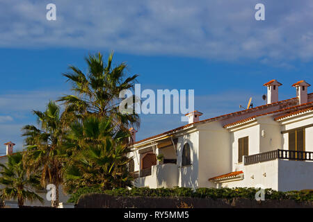 A row of Mediterranean beach summer cottages under blue sky. Palm trees and painted in white houses with tiled roofs. - Stock Photo