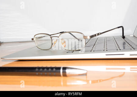 Desk with open notepad, pen, eye glasses, nicely placed on office table. Top view with copy space. Business still life concept with office stuff on ta - Stock Photo