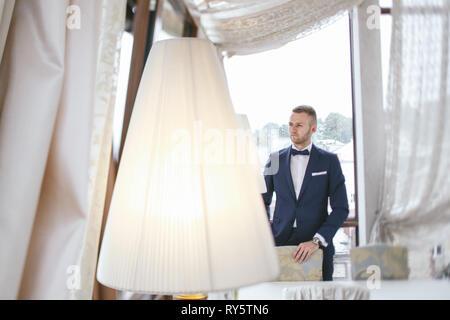 elegant groom in a hotel room - Stock Photo