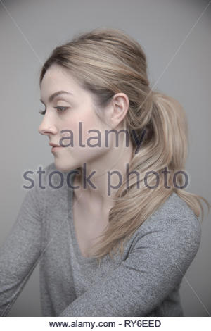 Portrait beautiful thoughtful young woman with blonde hair and nose ring - Stock Photo