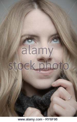 Close up portrait beautiful young woman with blonde hair and blue eyes looking up - Stock Photo