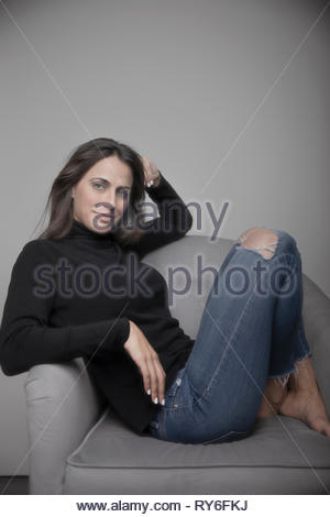 Portrait confident beautiful young woman in sweater and ripped jeans - Stock Photo