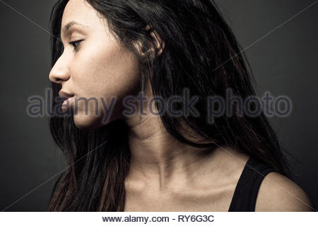 Profile portrait thoughtful beautiful young Jamaican woman with long black hair - Stock Photo