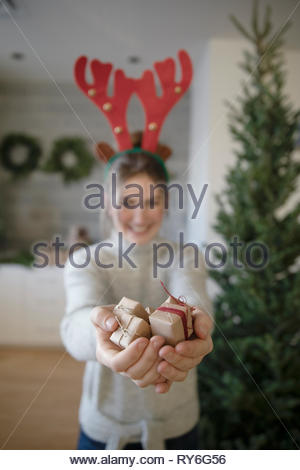 Portrait teenage girl in reindeer antlers holding small christmas gifts - Stock Photo