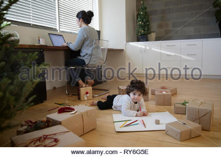 Toddler Latina girl coloring surrounded by christmas gifts behind mother working at laptop - Stock Photo
