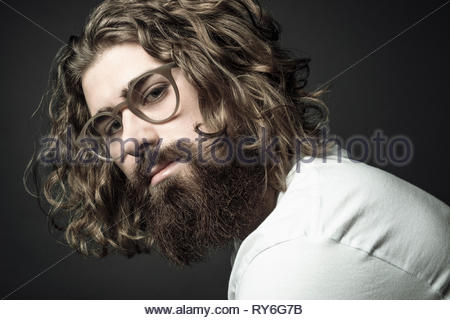 Portrait confident handsome young man with curly long hair and beard - Stock Photo
