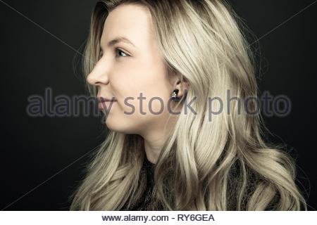 Profile portrait thoughtful beautiful young blonde woman looking away - Stock Photo