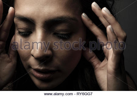Close up portrait beautiful Latina woman with head in hands looking down - Stock Photo