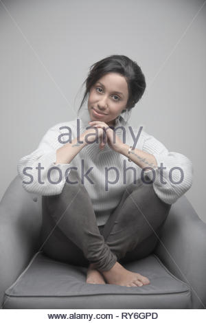Portrait confident beautiful young Jamaican woman in armchair - Stock Photo