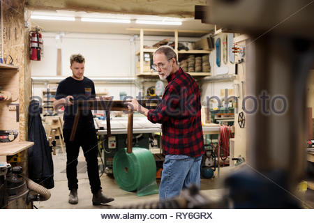 Male carpenters carrying coffee table in workshop - Stock Photo