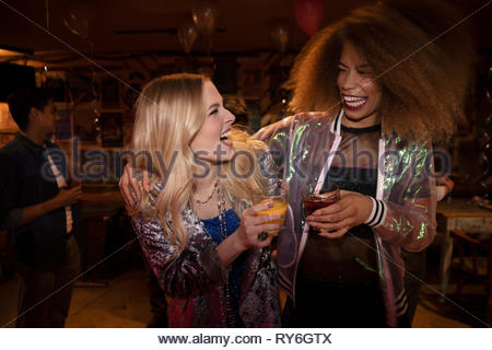 Young women friends drinking cocktails in nightclub - Stock Photo