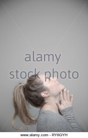 Happy beautiful young woman with blonde hair looking up - Stock Photo