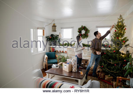Young couple decorating christmas tree in living room - Stock Photo