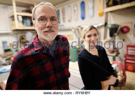 Portrait confident father and daughter in workshop - Stock Photo
