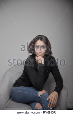 Portrait confident beautiful young brunette woman in ripped jeans - Stock Photo