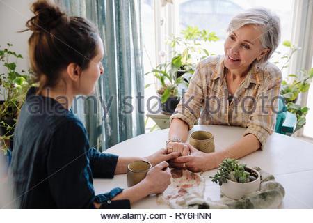 Mother and daughter holding hands and drinking coffee at table - Stock Photo