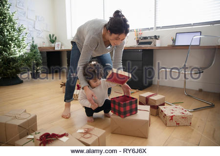 Latina mother and toddler daughter wrapping christmas gifts - Stock Photo