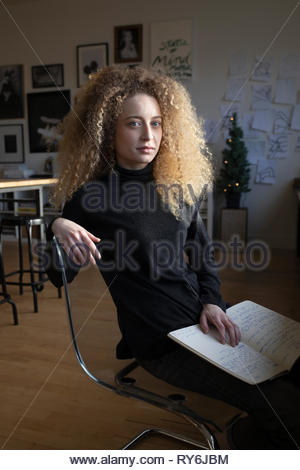 Portrait confident beautiful young blonde woman with curly hair working in studio - Stock Photo