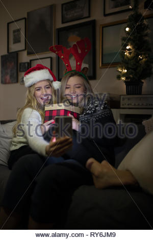 Festive young women friends celebrating christmas, taking selfie with camera phone - Stock Photo