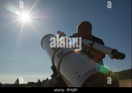 Low angle view of astronomer looking bright sun through telescope against clear sky during sunny day - Stock Photo