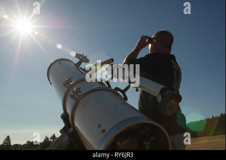 Low angle view of astronomer looking at bright sun while standing by telescope against clear sky during sunny day - Stock Photo