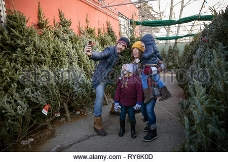 Happy family taking selfie, shopping for christmas tree at christmas market - Stock Photo