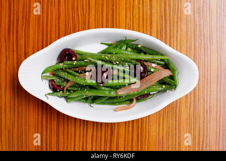 Overhead view of green beans with olives served in plate on wooden table - Stock Photo