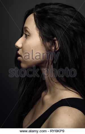 Profile portrait thoughtful beautiful young Jamaican woman looking away - Stock Photo