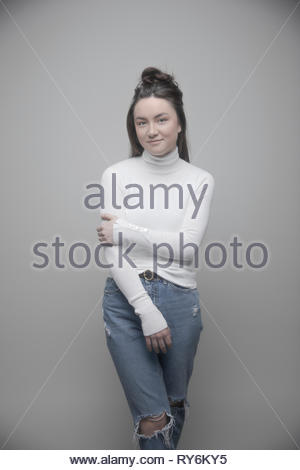 Portrait confident beautiful young brunette woman in ripped jeans and turtleneck sweater - Stock Photo