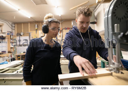 Woodworkers using saw in woodworking shop - Stock Photo