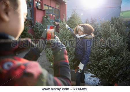 Girl with camera phone photographing sister holding christmas tree at christmas market - Stock Photo