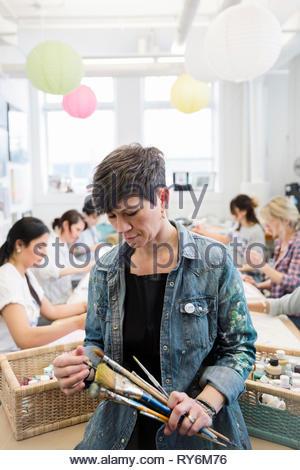 Female art teacher with paintbrushes in studio - Stock Photo