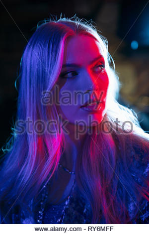 Portrait young woman in dark nightclub - Stock Photo