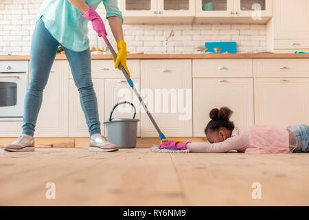 Funny curly girl lying on the floor while mother mopping the floor - Stock Photo
