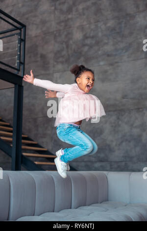 Daughter going crazy staying home alone and jumping - Stock Photo