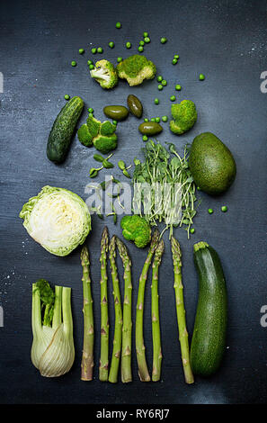 Flat lay of fresh green vegetables on black table - Stock Photo
