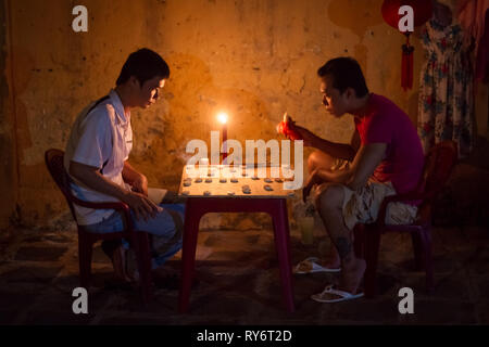 Men Playing Chinese Checkers Game By Candlelight in Hoi An, Vietnam - Stock Photo