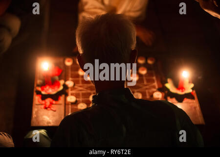 Old Vietnamese Man Playing Traditional Chinese Checkers By Candlight - Hoi An, Vietnam - Stock Photo