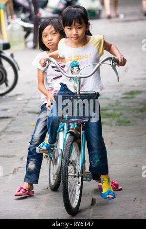 Young Vietnamese Girls Riding Large Bicycle Together on Streets of Hanoi, Vietnam - Stock Photo