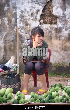 Teen Girl Selling Vegetables in Vientiane Market - Laos - Stock Photo