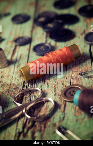 High angle view of various sewing items on old wooden table - Stock Photo