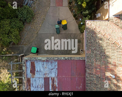 Pensioner active at home aerial view from above, taking the rubbish bins out. Aerial photography captured in Victoria, Australia. - Stock Photo