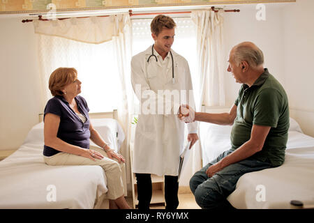 Young doctor greeting female patient and her husband in hospital room. - Stock Photo